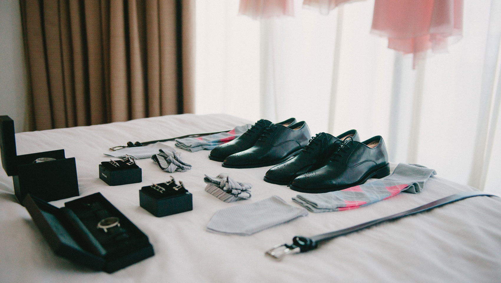 Wedding shoes, watch, tie, and belt on bed.