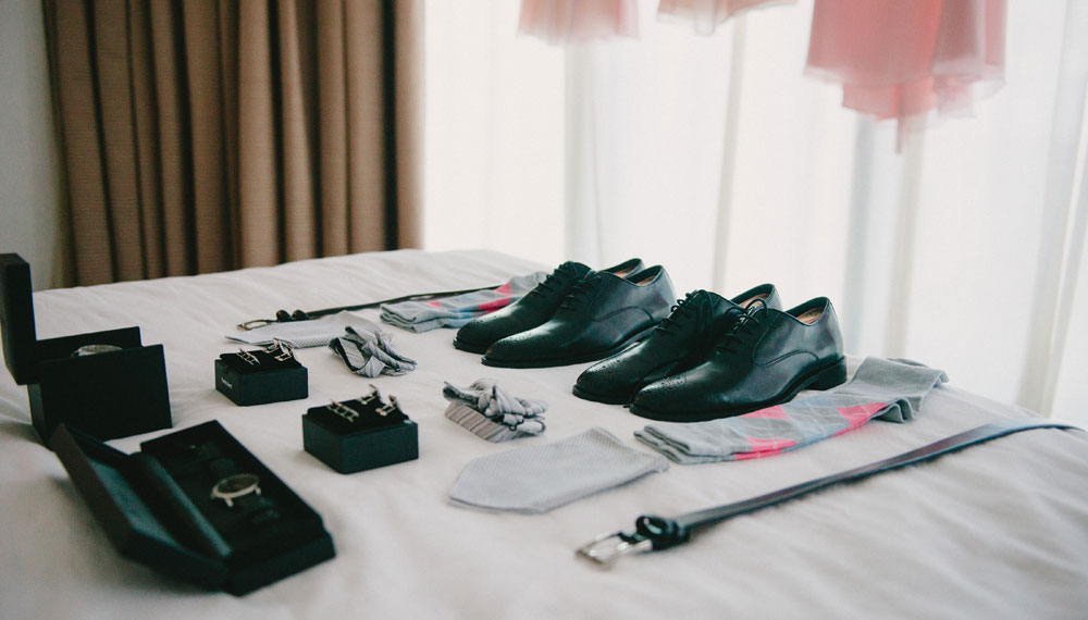 Wedding shoes, watch, tie, and belt on bed
