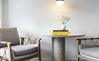 Light cream colored chair and desk with books and plant on top of desk